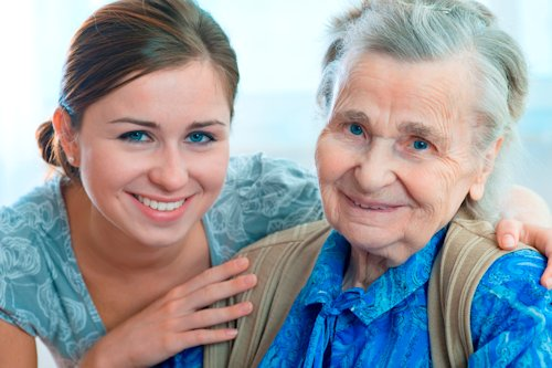 an old lady smiling while she is beside a young lady caring her